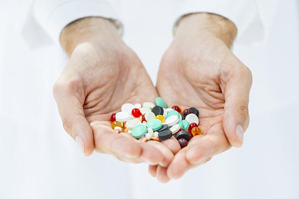 Imagem com uma pessoa segurando dezenas de comprimidos