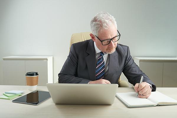 Homem idoso de óculos, concentrado, vestindo um terno cinza e uma gravata listrada, trabalhando em um notebook, com um tablet ao seu lado, escrevendo anotações em um caderno, se preparando para uma reunião importante.