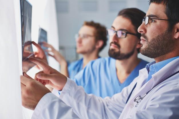 Foto de 3 homens, 1 médico e dois enfermeiros, onde o médico mostra o que parece ser uma radiografia a um dos enfermeiros.
