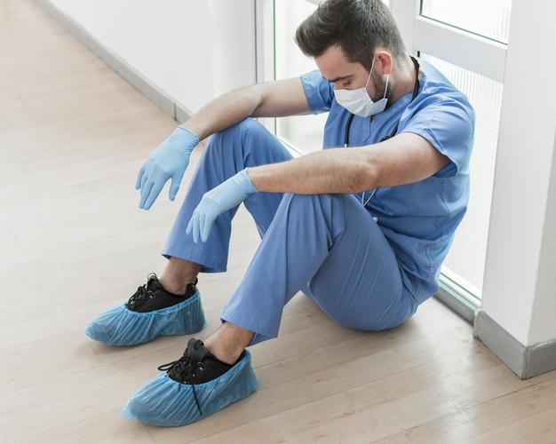 Médico cansado sentado no chão