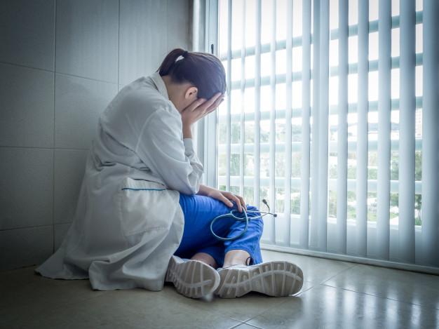 Médica deprimida sentado em desespero perto de uma janela de hospital